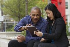 Bedrijfsman en vrouw buiten op hun onderbreking met hun tabletten royalty-vrije stock afbeelding