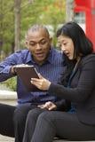 Bedrijfsman en vrouw buiten op hun onderbreking met hun tabletten stock afbeelding