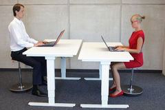 Bedrijfsman en vrouw in correcte zittingsposities in bureau stock foto's