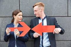 Bedrijfsman en vrouwenholdingspijlen tegen elkaar Royalty-vrije Stock Afbeeldingen