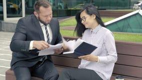 Bedrijfsman manager die documenten voor handtekening voorleggen aan zijn chef- vrouw stock videobeelden