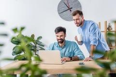 Bedrijfsmedewerkers die met laptop bij werkplaats in bureau werken Royalty-vrije Stock Foto