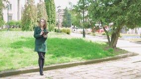 Bedrijfsmeisje die een tablet op groene straatachtergrond 4k gebruiken stock videobeelden