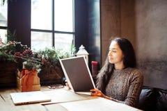 Bedrijfsmeisje die die het menu in restaurant bestuderen met Kerstmisdecor wordt verfraaid zit dichtbij het venster op bewolkte d royalty-vrije stock fotografie