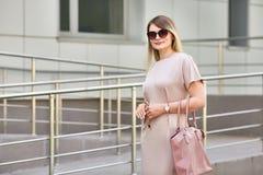 Bedrijfsmeisje die in zonnebril onderaan de straat lopen In zijn hand een autosleutel stock foto