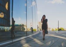 Bedrijfsmeisje op de achtergrond van het commerciële centrum die op de telefoon spreken Royalty-vrije Stock Afbeeldingen