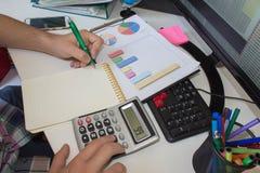 Bedrijfsmens of advocaataccountant die aan rekeningen werken gebruikend een calculator en schrijvend op documenten Stock Fotografie