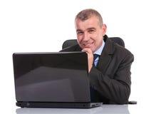 Bedrijfsmens bij laptop glimlachen voor de camera Royalty-vrije Stock Foto's