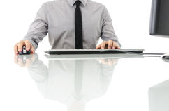 Bedrijfsmens bij zijn bureau die computer met behulp van Stock Foto's