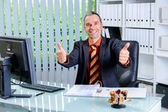 Bedrijfsmens bij zijn bureau met omhoog duimen Royalty-vrije Stock Foto's