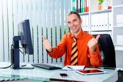 Bedrijfsmens bij zijn bureau met omhoog duimen Stock Afbeeldingen
