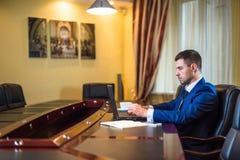 Bedrijfsmens in bureau met laptop Royalty-vrije Stock Afbeelding