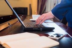 Bedrijfsmens in bureau met laptop Stock Foto's