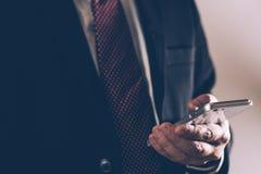 Bedrijfsmens in de Zwarte smartphone van het kostuumgebruik royalty-vrije stock fotografie