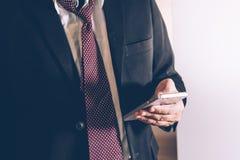 Bedrijfsmens in de Zwarte smartphone van het kostuumgebruik stock afbeeldingen