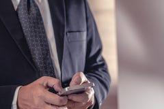Bedrijfsmens in de Zwarte smartphone van het kostuumgebruik stock afbeelding
