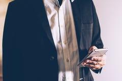 Bedrijfsmens in de Zwarte smartphone van het kostuumgebruik royalty-vrije stock foto
