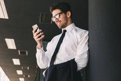 Bedrijfsmens dichtbij commercieel centrum die mobiele telefoon met behulp van stock foto's