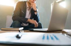 Bedrijfsmens die aan bedrijfsdocument en laptop op het werk werken stock foto's