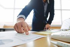 Bedrijfsmens die aan bedrijfsdocumenten, calculator en laptop op het werk werken stock foto