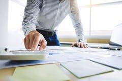 Bedrijfsmens die aan bedrijfsdocumenten, calculator en laptop op het werk werken stock fotografie