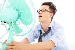 Bedrijfsmens die aan een hete de zomerhitte met ventilators lijden Stock Foto