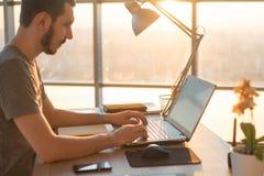 Bedrijfsmens die aan laptop bij bureau in bureau werken Stock Foto