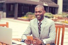 Bedrijfsmens die aan laptop werken die in openlucht op mobiele telefoon texting Stock Foto's