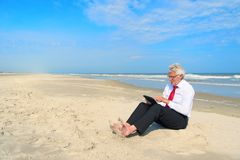 Bedrijfsmens die aan tablet bij het strand werken stock afbeelding