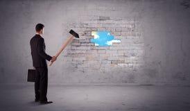 Bedrijfsmens die bakstenen muur met hamer raken Stock Fotografie