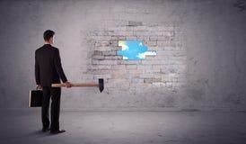 Bedrijfsmens die bakstenen muur met hamer raken Royalty-vrije Stock Afbeeldingen