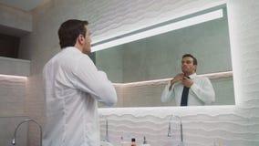 Bedrijfsmens die band in luxebadkamers dragen Gelukkige mens die binnenshuis kleden stock videobeelden