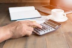 Bedrijfsmens die calculator met hete koffie gebruiken Stock Fotografie