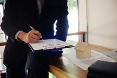 Bedrijfsmens die contract ondertekenen die onroerende goederenleeftijd maken behandelen Stock Foto
