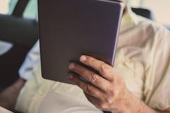 Bedrijfsmens die digitale tablet in auto gebruiken Stock Foto