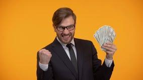 Bedrijfsmens die dollarbankbiljetten tonen en ja gebaar, hoog salaris, inkomen doen stock footage