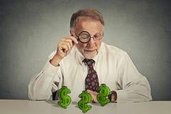 Bedrijfsmens die door vergrootglas dollartekens bekijken Stock Foto