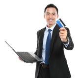 Bedrijfsmens die een creditcard en laptop houden Stock Afbeeldingen