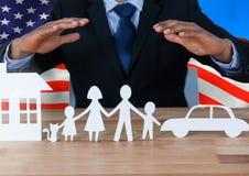 Bedrijfsmens die een document familie tonen tegen Amerikaanse vlag Stock Afbeeldingen