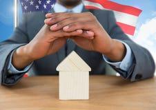 Bedrijfsmens die een huis behandelen tegen Amerikaanse vlag Stock Fotografie