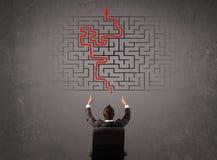 Bedrijfsmens die een labyrint en de uitweg bekijken Stock Foto's