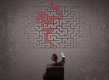 Bedrijfsmens die een labyrint en de uitweg bekijken Royalty-vrije Stock Afbeeldingen