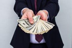 Bedrijfsmens die een Verspreiding van Contant geld over tonen witte uitstekende bedelaars stock afbeelding