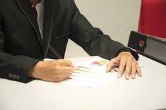 Bedrijfsmens die en bij bedrijfsgrafieken, grafieken en documentenachtergrond voor het analyseren van de zaken bekijken schrijven stock afbeeldingen