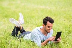 Bedrijfsmens die en op het groene gras met zijn apparaat glimlachen liggen stock afbeeldingen