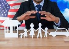 Bedrijfsmens die familie, auto en huis op papier tonen tegen Amerikaanse vlag Royalty-vrije Stock Fotografie