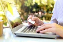 Bedrijfsmens die gegevens van een creditcard ingaan Het online winkelen op Internet die laptop met behulp van Stock Foto's