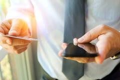 Bedrijfsmens die gegevens van een creditcard ingaan Het online winkelen op Internet die een mobiele telefoon met behulp van Stock Fotografie