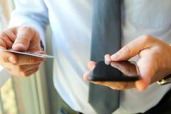Bedrijfsmens die gegevens van een creditcard ingaan Het online winkelen op Internet die een mobiele telefoon met behulp van Stock Foto's