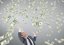 Bedrijfsmens die geldregen tegen grijze achtergrond bekijken Stock Afbeelding
